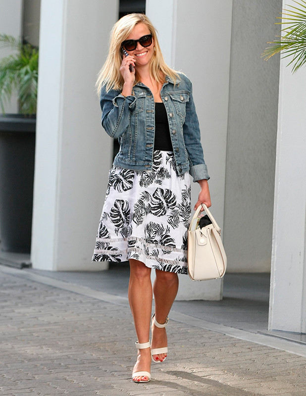 Reese Witherspoon chats on her cellphone as she leaves her office in Beverly Hills. She wore a distressed denim jacket, and carried a chic white leather handbag. 6 April 2015