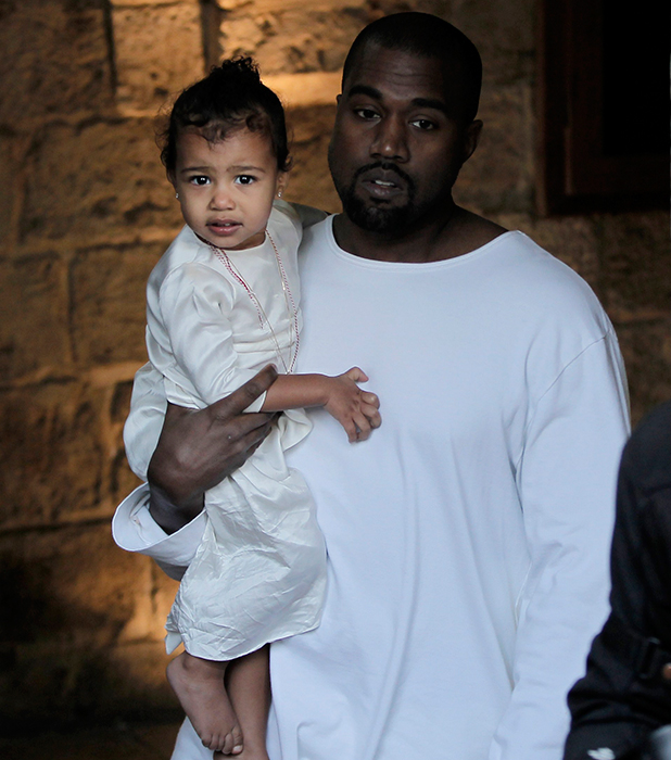 Kanye West, husband of US reality TV star Kim Kardashian, carries their daughter North, following a reported baptism ceremony at the Armenian St. James Cathedral in Jerusalem's Old City on April 13, 2015.