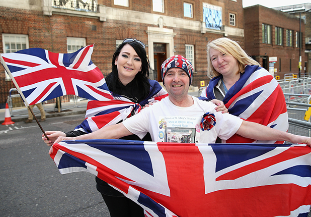 John Loughrey, Amy Thompson and Maria Scott (R) pose with Union Jack flags outside the Lindo Wing at St Mary's Hospital as they wait for the Duchess of Cambridge to go into labour on April 17, 2015 in London, England. Catherine, Duchess of Cambridge is expected to give birth at the Lindo Wing within the next couple of weeks to give a younger sibling to Prince George of Cambridge.