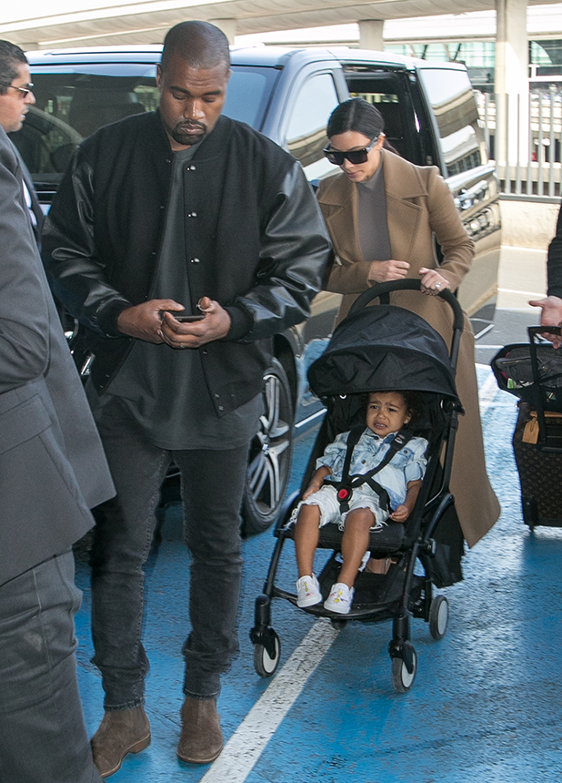Kim Kardashian West, her husband Kanye West and her daughter North west are seen at Charles-de-Gaulle airport on April 16, 2015 in Paris, France.