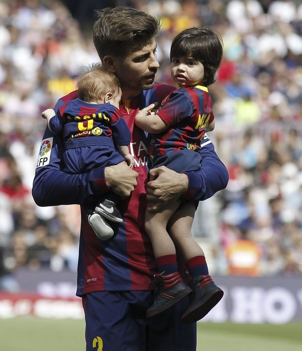 Barcelona's defender Gerard Pique with his children Sasha and Milan at the Spanish league football match FC Barcelona v Valencia CF at the Camp Nou stadium in Barcelona on April 18, 2015.