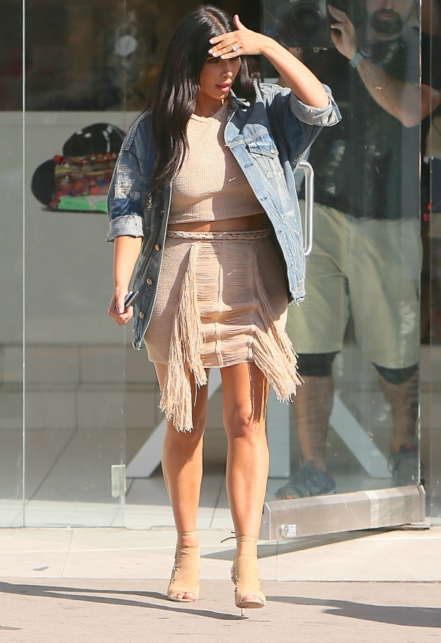 Kim Kardashian leaving the Dash store without her sunglasses and has to shield her eyes from the sun with her hand