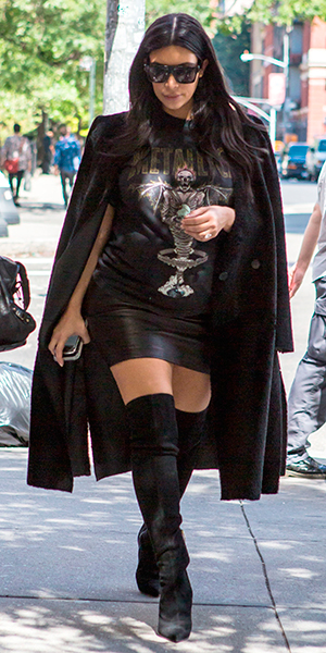 Kim Kardashian, wearing a long black coat, black knee high boots and a Metallica t-shirt, heads out for dinner with a friend in Soho during New York Fashion Week 09/11/2015