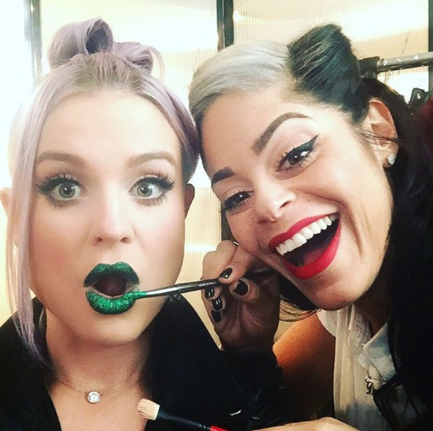 Kelly Osbourne poses with make-up artist Denika Bedrosian while having green, glittery lips painted on, 12 October 2015