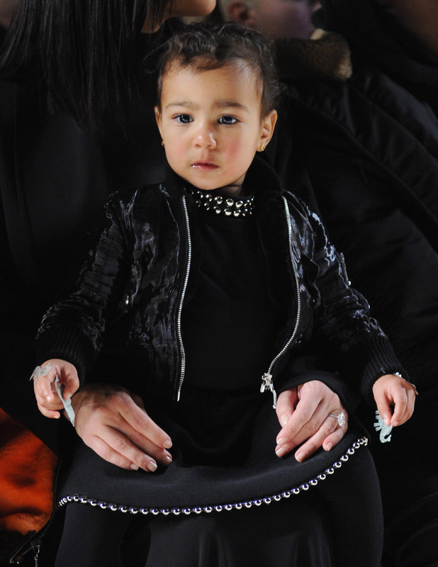 North West wearing black dress and matching bomber jacket on the front row at Alexander Wang, New York, 21st December 2015