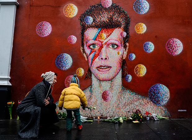 Floral tributes are left beneath a mural of British singer David Bowie, painted by Australian street artist James Cochran, aka Jimmy C, following the announcement of Bowie's death, in Brixton, south London, on January 11, 2016. British music icon David Bowie died of cancer at the age of 69, drawing an outpouring of tributes for the innovative star famed for groundbreaking hits like 'Ziggy Stardust' and his theatrical shape-shifting style. AFP PHOTO / CHRIS RATCLIFFE RESTRICTED TO EDITORIAL USE, MANDATORY MENTION OF THE ARTIST UPON PUBLICATION, TO ILLUSTRATE THE EVENT AS SPECIFIED IN THE CAPTION / AFP / CHRIS RATCLIFFE (Photo credit should read CHRIS RATCLIFFE/AFP/Getty Images)