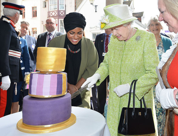 Britain's Queen Elizabeth II cuts into a cake made by Nadiya Hussain (L), winner of the Great British Bake Off during a 'walkabout' on her 90th birthday in Windsor, west of London, on April 21, 2016.