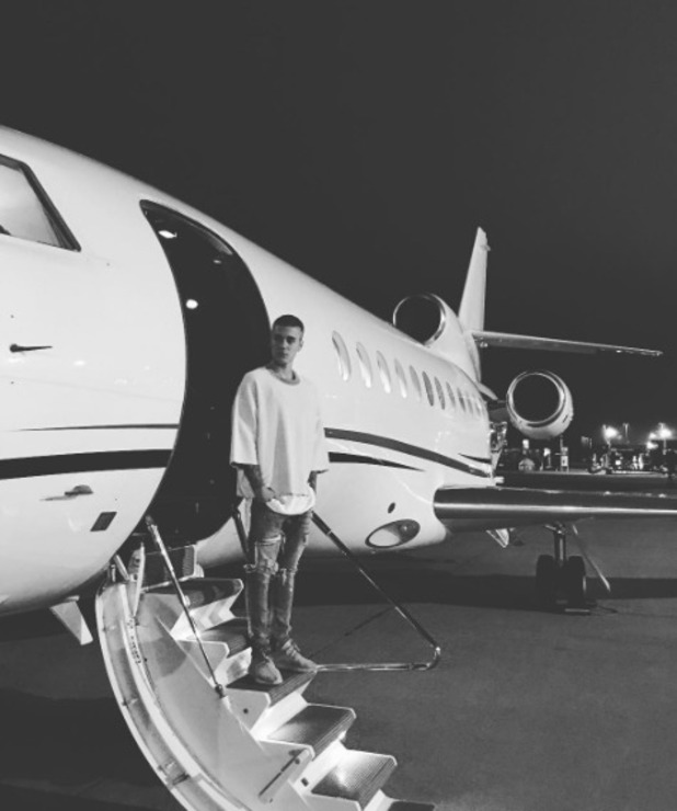 Justin Bieber shows off his new hair by a plane