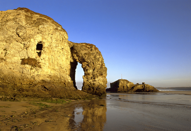 The great rock formations at Droskyn Point, Perranporth, showing the Chapel Rock with the Arch Rock reflected in wet sand