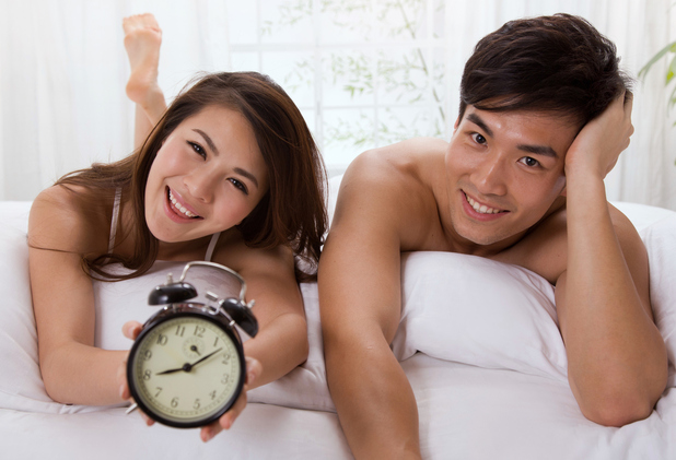 Couple in bed holding an alarm clock