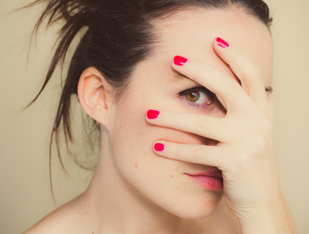 Woman feeling awkward and holding her hand over her face